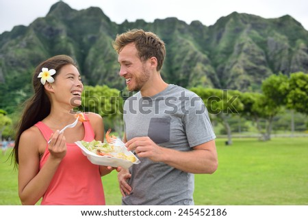 Hawaii food travel couple eating garlic shrimps on Oahu's North Shore. Popular Hawaiian shrimp food truck meal on road trip concept. - stock photo