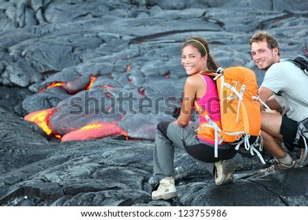Hawaii lava tourist on hike. Tourists hiking near flowing lava from Kilauea volcano around Hawaii volcanoes national park, USA. Multiethnic couple. - stock photo