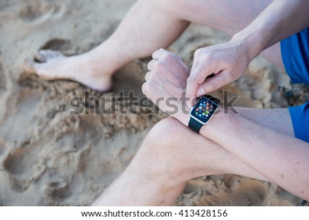 Hawaii, USA - April 30, 2016: Man Using App on Apple Watch While Outside. Multiple Apps View.