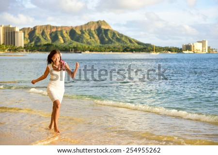 Hawaii woman having fun on Waikiki beach, Honolulu. Asian adult tourist running of joy on famous destination Waikiki beach at sunset with Diamond Head in the background. Wearing Hawaiian lei necklace. - stock photo