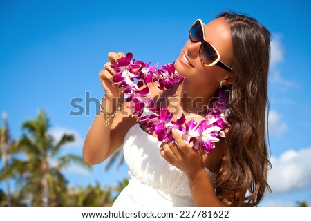 Hawaii woman with flower lei garland of pink orchids. Beautiful smiling woman in white dress. Welcoming Lei on the hawaiian island Honolulu. - stock photo