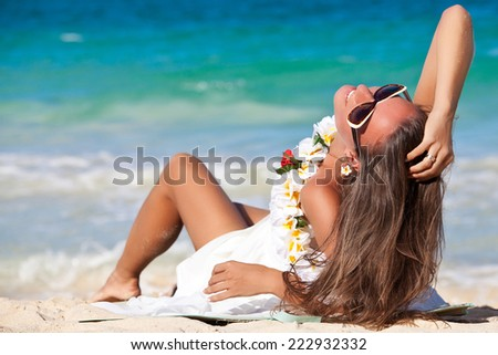 Hawaii woman with flower lei garland of white plumeria. Beautiful smiling woman in white dress on beach on the hawaiian Honolulu island. - stock photo