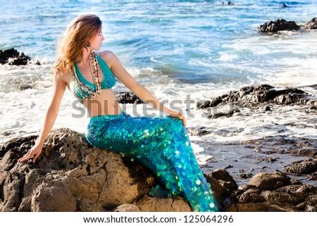 Hawaiian Beautiful Mermaid on Lava Rocks at the Ocean - stock photo