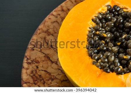 Hawaiian papaya fruit cut in half with seeds on a brown plate, dark background - stock photo