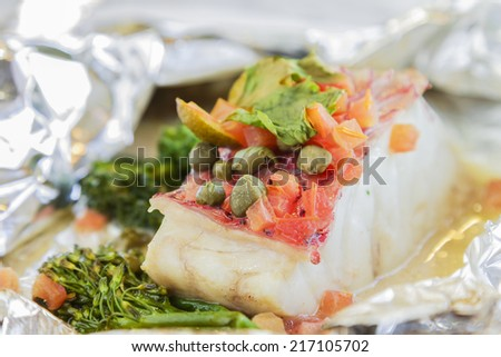 Hawaiian pink snapper cooked in a white wine butter sauce with broccolini, and spices - stock photo