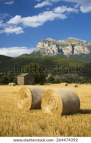 Hay bails with sweeping views of Parque National de Ordesa near Ainsa, Huesca, Spain in Pyrenees Mountains - stock photo