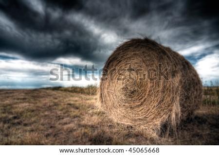 Hay bale against ominous sky - stock photo
