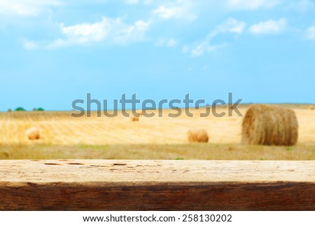 hay bale field blur tabletop wooden background shallow DOF - stock photo