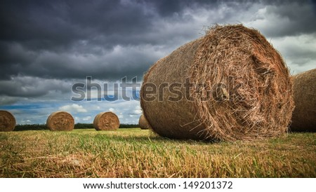 Hay bale on a field on a cloudy dramatic day