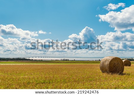 Hay bales on a farm along the ocean with the Confederation Bridge in the background (Prince Edward Island, Canada) - stock photo