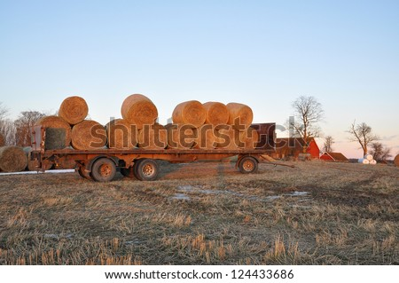 hay bales on a trailer a frosty winter evening. - stock photo