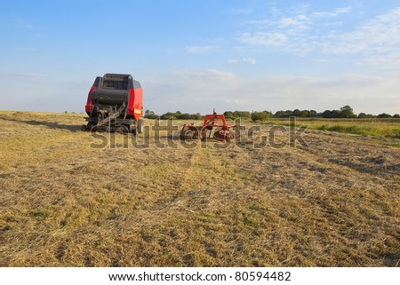 hay turning equipment and baler in a newly cut hay field on a river bank under a blue summer sky