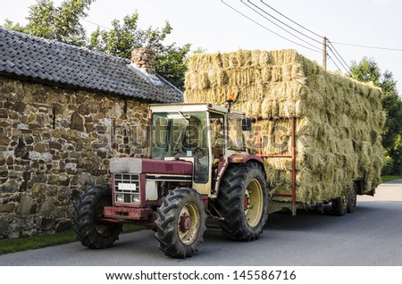 Haymaking, tractor with hay cart loaded with hay bales on a road - stock photo