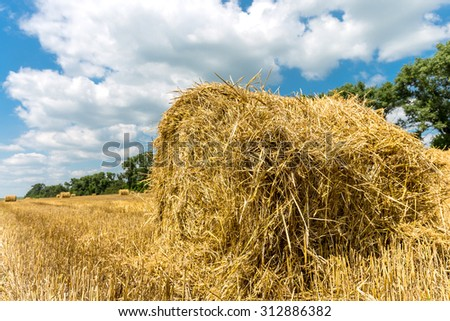 Hayroll on crop field n nice sunny day - stock photo