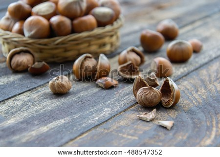 Hazelnut kernels and whole hazelnuts on old brown table, selective focus