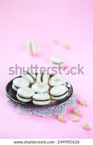 Hazelnut Macarons filled with Chocolate Ganache on a black plate and lace napkin, on a light pink background. - stock photo