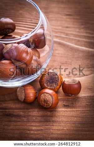 hazelnuts and transparent round glass bowl on vintage wooden board food and drink still life  - stock photo