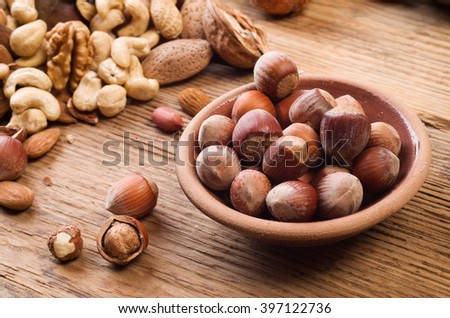 Hazelnuts in a  bowl on a wooden background