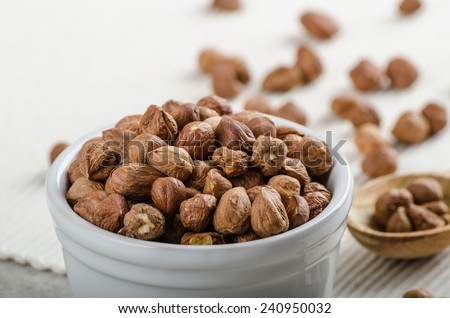 Hazelnuts in a bowl, spoon on the towel, wood, focus on bowl - stock photo