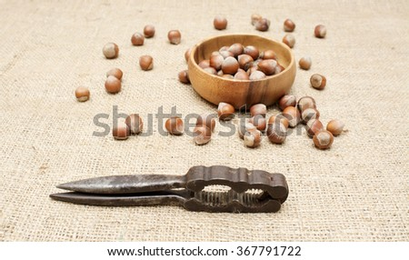 Hazelnuts in a wooden bowl on burlap with nutcracker.  - stock photo