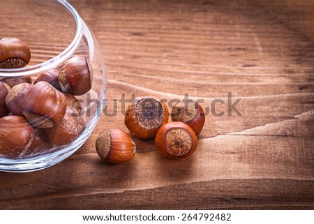 hazelnuts in glass and on vintage wooden board food and drink concept  - stock photo