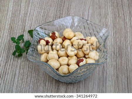 Hazelnuts in the bowl on the wood background ready for eat