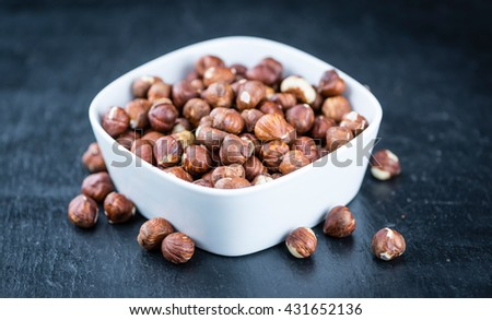 Hazelnuts on a slate slab (selective focus; close-up shot) - stock photo