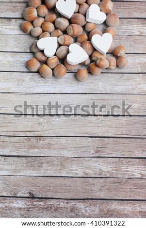 Hazelnuts on the wooden background. Hazelnuts and wooden hearts. White wooden hearts. Shabby hazelnuts.  - stock photo