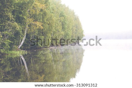 Hazy landscape on a cold morning by the lake. The forest is making a beautiful reflection in the still water. Image has a vintage effect applied. - stock photo