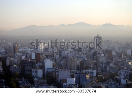 Hazy skyline of Mexico City at dawn, smog covering suburban hills