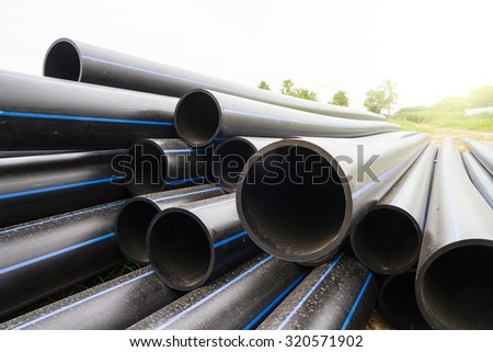HDPE pipe for water supply at construction site in morning light - stock photo