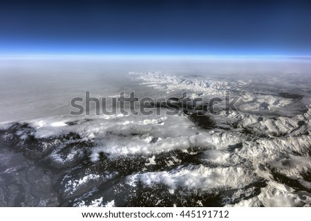 HDR Aerial photo of the landscape with clouds, snowy mountains and view stretching all the way to the horizon