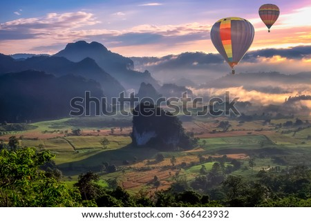 HDR beautiful scenary in the north part of Thailand over the valley of mountain at sun rise beautiful color of mist, hot air balloon flying in sky (selective focus and white balance shifting applied) - stock photo