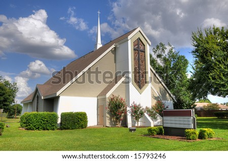HDR image of a beautiful Christian church with white steeple cross and blue sky - stock photo