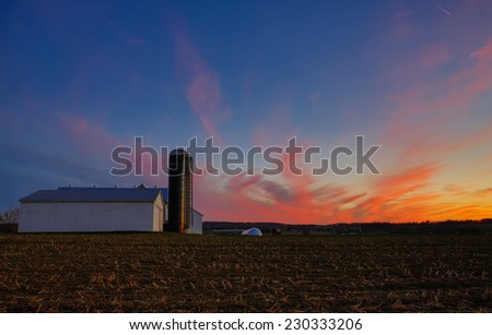 HDR image of barn and silo at sunset against vivid colorful evening sky. - stock photo