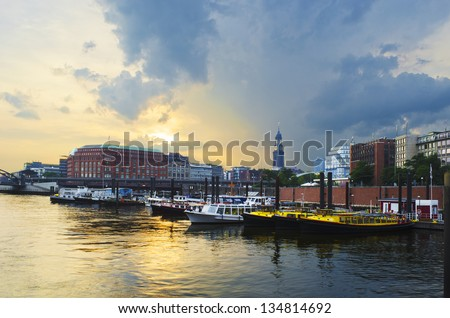 HDR image of the harbor of Hamburg, Germany. A thunder storm is approaching while the sun sets. The St. Michaelis church, also called Michel, can be seen. - stock photo