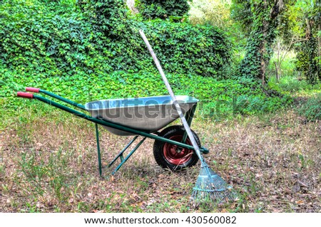 hdr of wheelbarrow in a garden and a rake