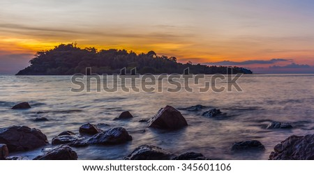 HDR rock on sea beach at sunset - stock photo