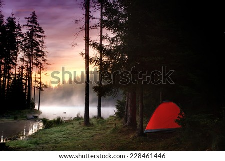 HDR sunrise landscape near forest lake, red tent on the beach and colorful sky  - stock photo