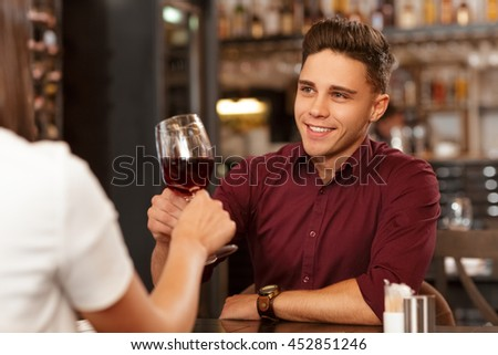 He adores his woman. Handsome man gives a toast on a romantic date at the restaurant smiling cheerfully to his woman - stock photo