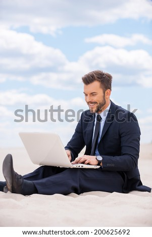 He found a peaceful place to work. Handsome young man in formalwear working on laptop and smiling while sitting on sand in desert