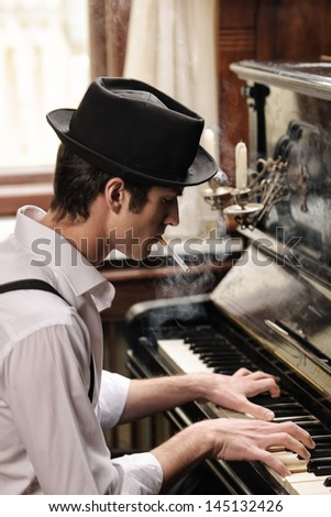 He got his own technique. Profile of handsome young men playing piano and smoking cigarette - stock photo