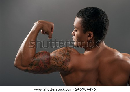 He got perfect body. Rear view closeup portrait of young shirtless African man showing his bicep with tattoo while standing against grey background  - stock photo
