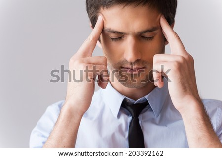 He got stressful job. Young man in shirt and tie touching head with fingers and keeping eyes closed while standing against grey background - stock photo