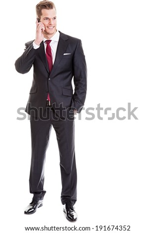He has to answer an important phone call! - Full length shot of a relaxed young businessman chatting on a phone, isolated on white - stock photo