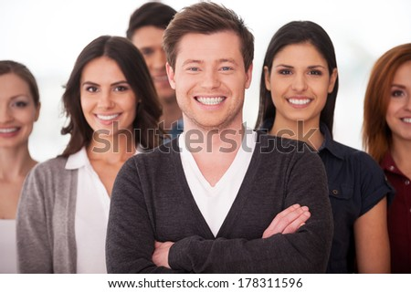 He is a real team leader. Confident young man keeping arms crossed and smiling while group of people standing on background - stock photo