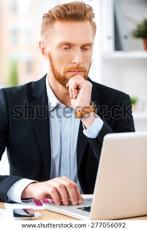 He is always hard at work. Concentrated bearded businessman working on laptop and holding hand on chin while sitting at his working place - stock photo