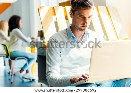 He is always hard at work. Concentrated young man working on laptop while his colleagues working in the background  - stock photo