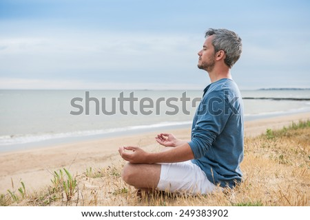 He is meditating with his hands turn up to the sky. - stock photo