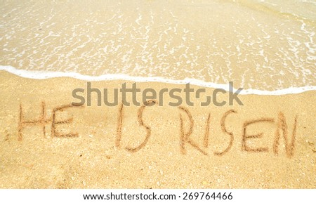 He is risen written in the sand for easter on the shoreline - stock photo